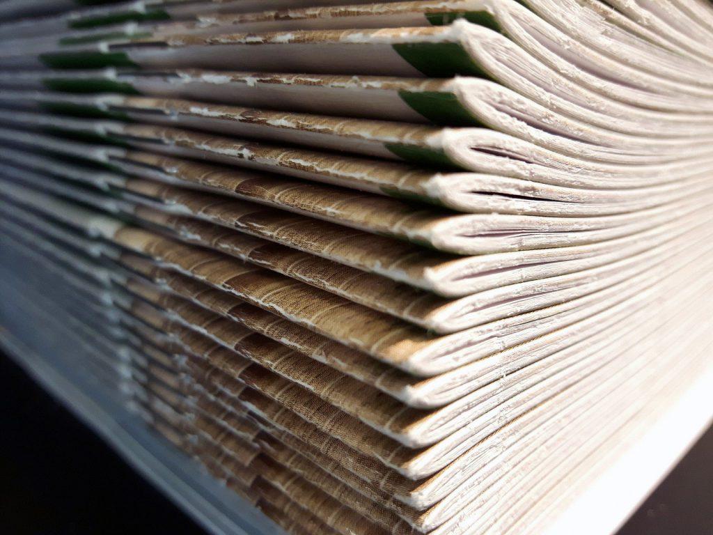 Na czarnym tle kilkanaście czasopism ułożonych jedno na drugim