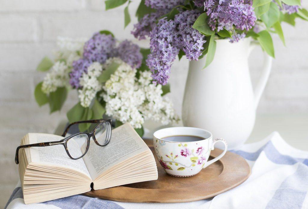 na stoliku leży rozłożona książka. Na książce  okulary. Obok filiżanka kawy oraz  biały i fioletowy bez w białym wazonie